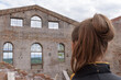 Girl on the ancient ruins of the building. View from the back. Old red brick wall. Vaulted windows. Concept tourism in medieval castle, antiquity.
