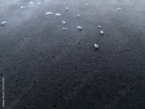 Fotomural waterdrops macro image on dark grey porous concrete on the holocaust memorial in