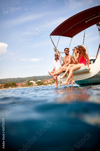 Friends sitting on stern of a yacht