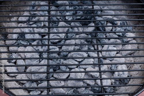 Photo Close-up of BBQ grill pit hot charcoal briquettes, food Background or texture