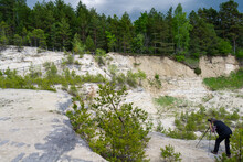 Photographer Taking Picture Of Limestone Wall In Former Open-pit Quarry. Stormy Weather. Nowiny, Susiec, Poland, Europe.