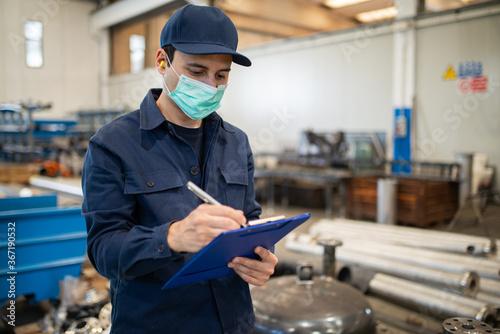 Fototapeta Industrial worker writing on a document obraz