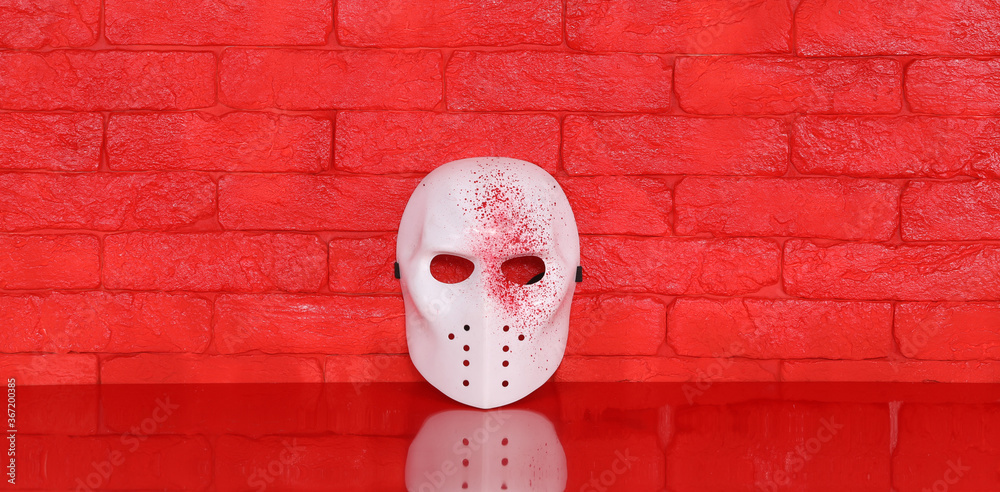 Fototapeta white killer mask on red table, red brick wall background