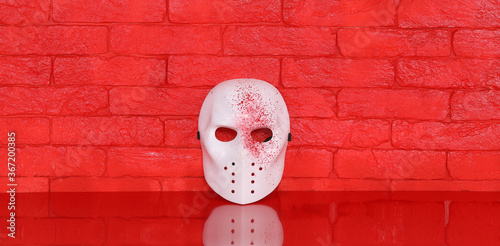 white killer mask on red table, red brick wall background Canvas Print
