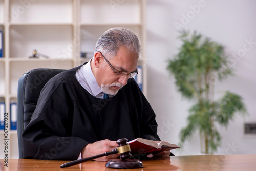 Old male judge working in courthouse Canvas Print