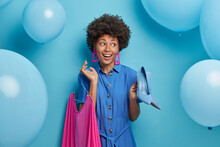Glad Positive Afro American Lady Chooses Outft For Date, Holds High Heeled Blue Shoes And Rosy Dress On Hangers, Prepares To Party And Celebration, Poses Over Blue Background With Inflated Balloons