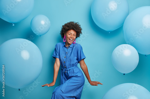 Fototapeta Carefree joyful curly woman dances happily, dressed in blue dress, chills at party around inflated helium balloons, feels playful, enjoys favorite holiday, has upbeat festive mood