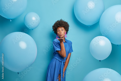 Tela Photo of romantic curly haired woman blows kiss to lover, has party mood, dressed in pretty dress, poses against studio wall with balloons