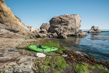 Kayak On The Beach Overlooking Pacific Ocean And Rocky Cliffs With Flock Of Birds, California