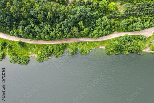 beautiful aerial top view of dirt road between green summer forest and lake Canvas-taulu