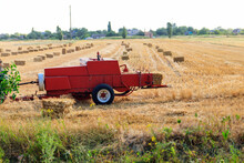 Rectangular Baler Discharges A Straw Bale In A Field During The Harvesting Process