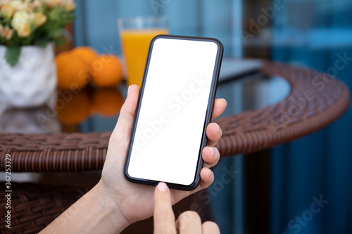 Obraz female hands holding phone with isolated screen on background cafe - fototapety do salonu