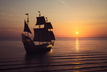 ( 3D Illustration, Rendering ) VIntage Black Pirate Ship Sailing Towards The Sunset.