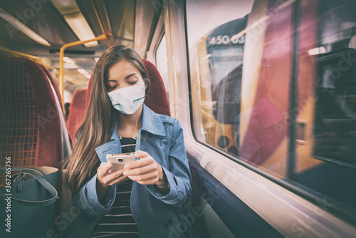 Obraz Mask wearing mandatory inside public spaces for transport such as train station and bus. Asian woman passenger using mobile phone with face covering wear sitting indoors on commute. - fototapety do salonu