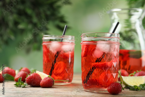 Obraz Refreshing drink with strawberry and lime on wooden table - fototapety do salonu