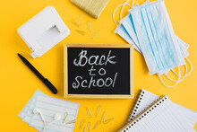 """Blackboard With Written Text """"back To School"""", Protective Medical Face Masks And School Stationery On Yellow Background. Education During Covid 19 Pandemic. Flat Lay"""