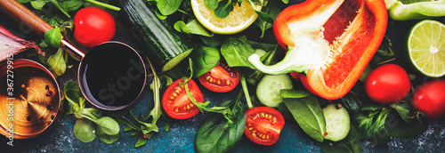 Fresh helthy food cooking or salad making ingredients on dark background with rustic wooden board. Diet or vegetarian food concept. Panoramic banner with copy space