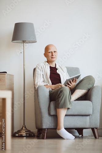 Minimal full length portrait of bald adult woman holding book and looking at camera pensively while sitting in comfy armchair at home, alopecia and cancer awareness