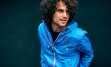 Fototapeta Na drzwi - Closeup outdoor image of Caucasian man with curly hair posing against grey wall outside in blue rain coat. Student male resting in the street on a rainy day. Happy guy poses against black wall.