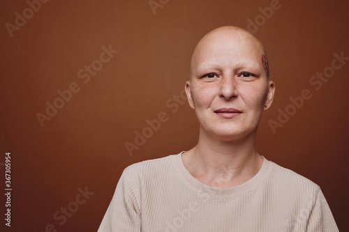 Fotografia Minimal head and shoulders portrait of bald woman smiling at camera while posing