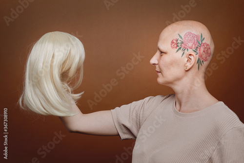 Fototapeta Side view portrait of confident bald woman holding wig of blonde hair against br