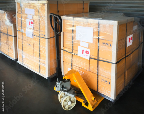 Fototapeta Hand pallet truck with a large shipment pallet goods. Cargo export & Shipping warehouse, Logistics and transportation. obraz