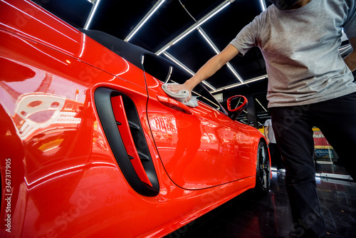 Obraz Car service worker polishing car with microfiber cloth. - fototapety do salonu