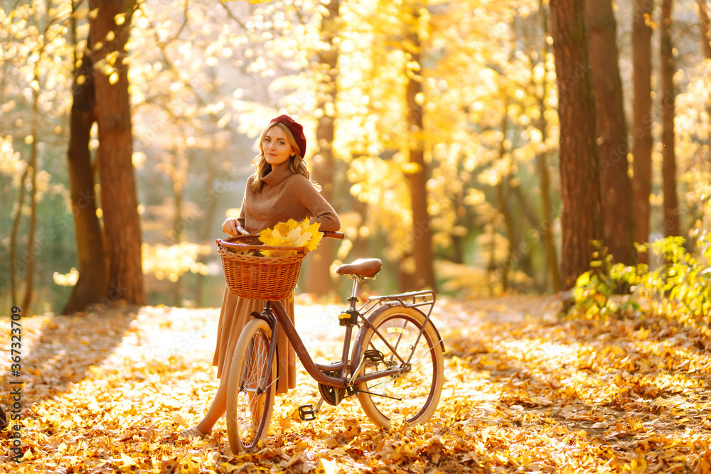Fototapeta Young smiling girl with a bicycle walks in the autumn forest at sunset. - obraz na płótnie