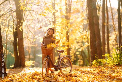 Fototapeta Нappy young woman having fun with leaves in autumn park.  obraz na płótnie