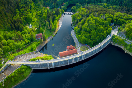 Fototapeta Dam and hydroelectric water power station. Concept of the clean energy. Aerial panoramic view of stone dam at reservoir in mountains. Drone shot at Pilchowice Lake, Poland obraz