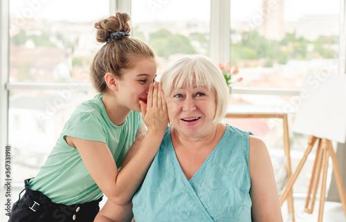 Fototapeta Little girl whispering secret to grandmother obraz