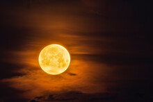 Bright Yellow Moon In Dark Sky And Illuminates The Clouds