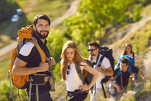 Male Backpacker With His Friends Climbing To Mountain Top. Team Of Hikers Mountaineering On Summer Vacation Outside