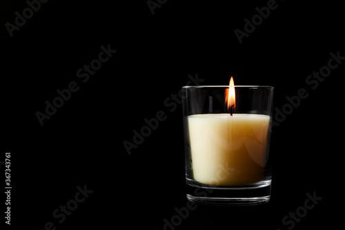 Obraz White wax burning candle in glass Isolated on black background, mock up - fototapety do salonu