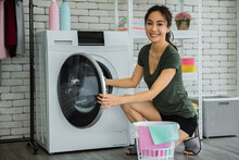 Young Woman Doing Laundry At H...