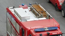 Top View Of Blinking Blue Fire Truck Siren, Red Fire Engine Arriving To The Place Of Fire Alarm, Rescue Fire Brigade With Different Equipment For Saving Operations. Emergency Sign And Firefighters
