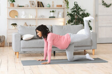 Pregnant African Woman Exercising At Living Room