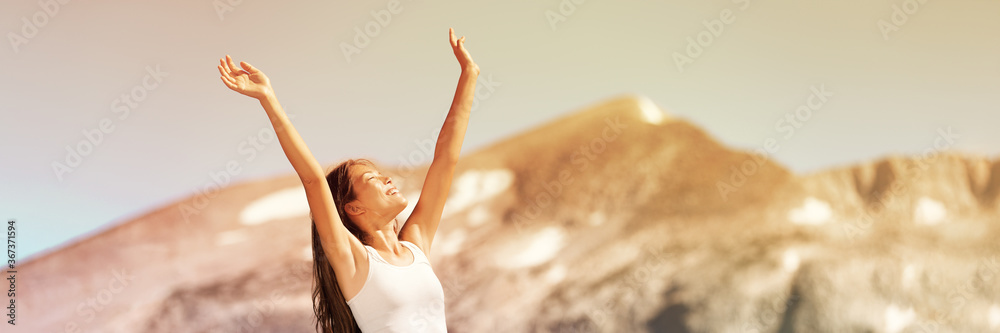 Fototapeta Happy free woman excited with arms up enjoying summer sunshine freedom on nature travel outdoor mountains landscape banner panorama. Smiling Asian girl.
