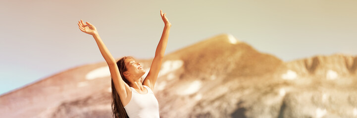 Happy free woman excited with arms up enjoying summer sunshine freedom on nature travel outdoor mountains landscape banner panorama. Smiling Asian girl.