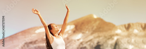 Fototapeta Happy free woman excited with arms up enjoying summer sunshine freedom on nature travel outdoor mountains landscape banner panorama. Smiling Asian girl. obraz