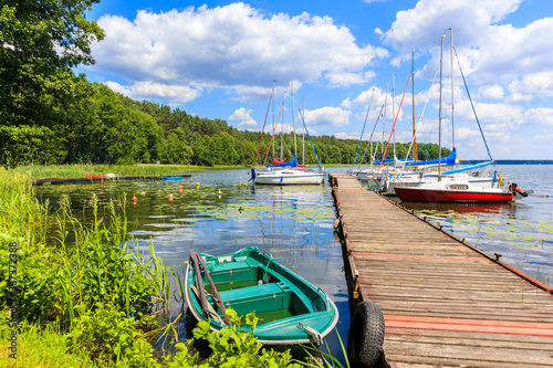 Fishing boat and yacht boats at pier on lake shore in Karwica village port on sunny summer day, Mazury Lake District, Poland