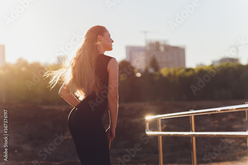 Fotografie, Obraz Happy successful sportswoman raising arms to the sky on golden back lighting sunset summer