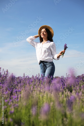 Young woman with lavender bouquet in field on summer day