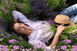 canvas print picture - Young woman lying in lavender field on summer day