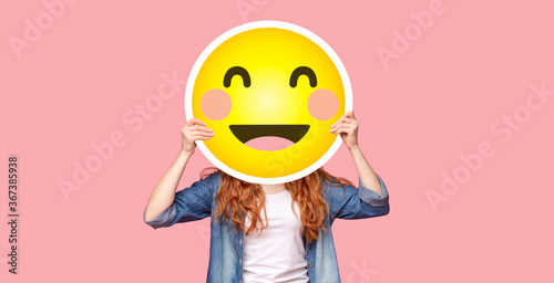 Redhead girl hiding her face behind happy emoji smile - 367385938