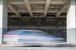 Schnell vorbeifahrendes Auto an einem großen Parkhaus eines Flughafens