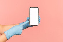 Profile Side View Closeup Of Human Hand In Blue Surgical Gloves Holding And Showing Smart Phone And Pointing At Empty Display. Indoor, Studio Shot, Isolated On Pink Background.
