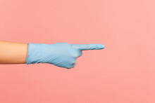 Profile Side View Closeup Of Human Hand In Blue Surgical Gloves Showing Or Pointing Ot Something With Finger. Indoor, Studio Shot, Isolated On Pink Background.