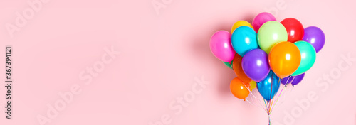 Foto Bunch of bright balloons on pink background, space for text