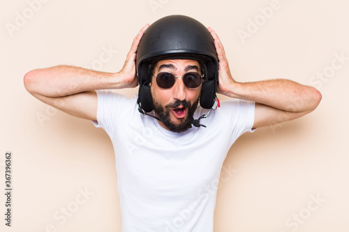 young cool bearded man surprised with a helmet. motorbike rider Fototapet